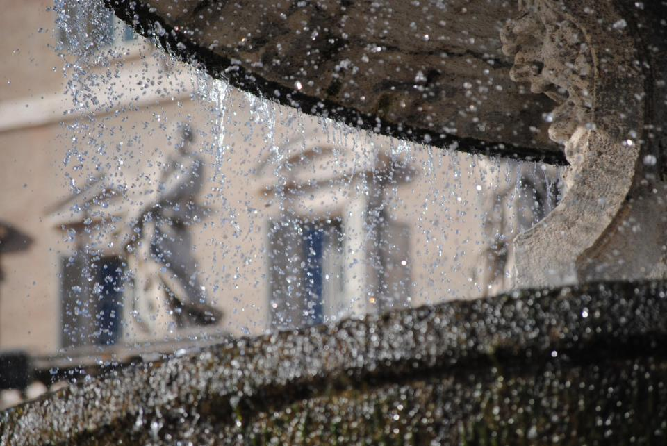 A view of a statue through a fountain at St Peters Basillica, Vatican